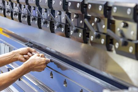 The technician operator use hydraulic bending machine. The sheet metal manufacturing process.