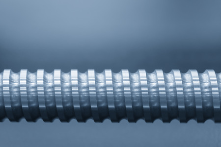Nahaufnahme des Ersatzteils der Leitspindelwelle der CNC-Maschine in der hellblauen Szene. Das hochpräzise CNC-Ersatzteil