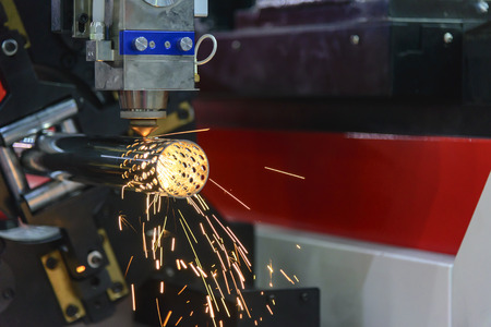 The CNC fiber laser cutting machine cutting the stainless pipe or tube  with the sparking light. Modern sheet metal manufacturing process. Stock Photo