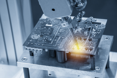 The soldering robot welding the circuit board in the light blue scene with the lighting effect. Zdjęcie Seryjne