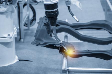 Die Schweißrobotermaschine zum Schweißen von Automobilteilen in der hellblauen Szene. Industrie 4.0-Konzept für moderne Fertigungsverfahren.