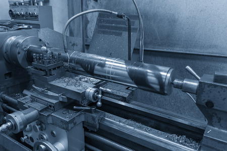 The  operation of lathe machine cutting the steel shaft in the light blue scene with the coolant fluid.