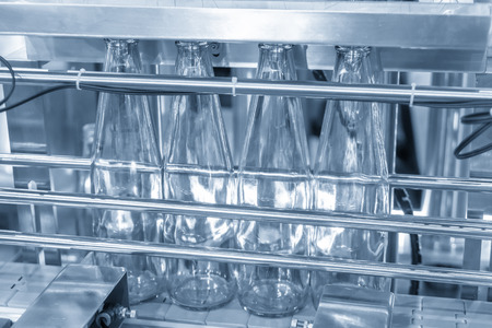 The new glass bottles on the conveyor belt at the drinking water factory. Drinking water manufacturing process. 写真素材 - 111563175