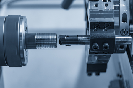 The CNC lathe or turning machine boring the hole at the metal pipe in the light blue scene.Hi-technology manufacturing process.