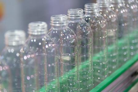 Las nuevas botellas de plástico en la cinta transportadora de la fábrica de agua potable. Proceso de fabricación de agua potable. Foto de archivo