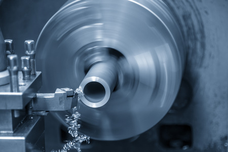 The lathe machine cutting the steel tube .Metal working in factory. Stock Photo