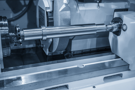 The metal shaft on the cylindrical grinding machine.The automotive part manufacturing process.