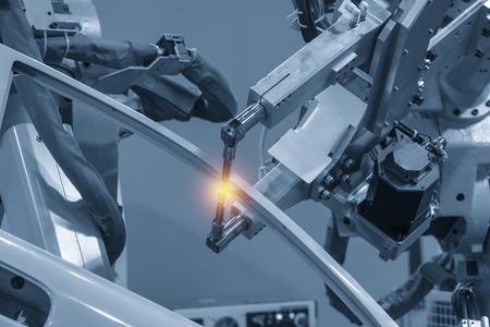 Die Schweißrobotermaschine schweißt die Automobilteile mit Lichteffekt. Industrie 4.0-Konzept für modernen Fertigungsprozess. Standard-Bild
