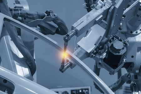 Zautomatyzowana spawarka spawająca części samochodowe z efektem świetlnym. Koncepcja Industrial 4.0 dla nowoczesnego procesu produkcyjnego. Zdjęcie Seryjne