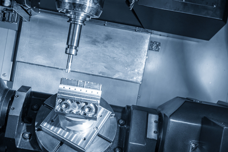 The 5-axis CNC milling machine cutting the aluminium cylinder block part.The hi-precision automotive manufacturing process.