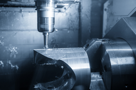 The  5-axis CNC machining center chamfering the hole by chamfering tools  .The 5 axis CNC milling machine cutting the automotive part with ball end mill tool. Stock Photo