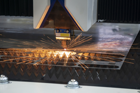 The CNC fiber laser cutting machine cutting the metal plate with the sparking light. The sheet metal working operation.