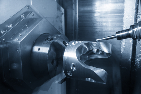 The  5-axis CNC machining center  cutting the automotive part with solid ball end mill. The hi technology manufacturing process of automotive parts. Stock Photo