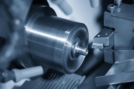 Die CNC-Drehmaschine schneidet das Gewinde an den Metallteilen. Der hochtechnologische Herstellungsprozess von Automobilteilen durch Drehmaschine.