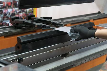 El operador técnico utiliza una máquina dobladora hidráulica. El proceso de fabricación de chapa. Foto de archivo