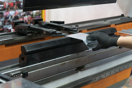 The technician operator use hydraulic bending machine. The sheet metal manufacturing process.