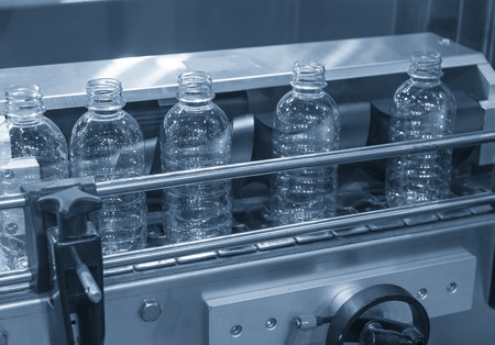 The plastic bottles on the conveyor belt at the drinking water factory. Drinking water manufacturing process.