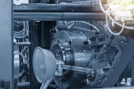 El brazo robótico mantiene la pieza de soplado de plástico lejos de la máquina de inyección. La alta tecnología para el proceso de inyección.