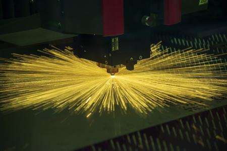 La macchina da taglio laser in fibra CNC che taglia la piastra metallica con la luce scintillante. L'operazione di lavorazione della lamiera. Archivio Fotografico