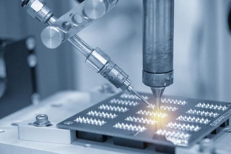 Der Lötroboterbetrieb mit elektronischer Platine. Herstellungsprozess von elektronischen Leiterplatten.