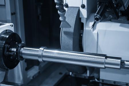 Die Rundschleifmaschine in der hellblauen Szene mit der Stahlwelle. Der Herstellungsprozess von Automobilteilen.
