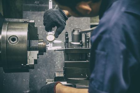 The lathe machine operator measure the inside diameter of metal part with vernier calliper. The retro scene of workshop operation.