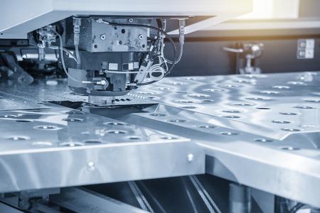 De hi-speed CNC-ponsmachine in lichtblauw tafereel. Moderne metaalbewerking productieproces door ponsmachine. Stockfoto