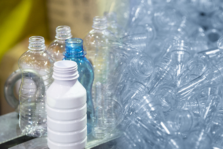 The abstract scene of preform shape and  plastic bottles product. Drinking water bottle manufacturing process.