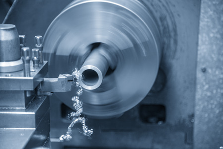 The lathe machine cutting the metal tube parts. The metal working manufacturing process. Archivio Fotografico