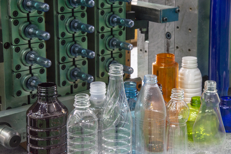 The plastic bottles and injection mold in background. PET plastic bottle manufacturing concept.