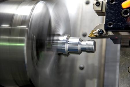 La macchina del tornio di CNC che taglia il filo alle parti metalliche. Il processo di produzione di componenti automobilistici ad alta tecnologia mediante tornio.