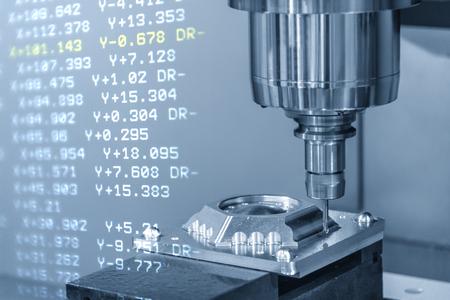 Il centro di lavoro CNC con lo sfondo dei dati G-code. La fresatrice CNC che taglia le parti dello stampo.