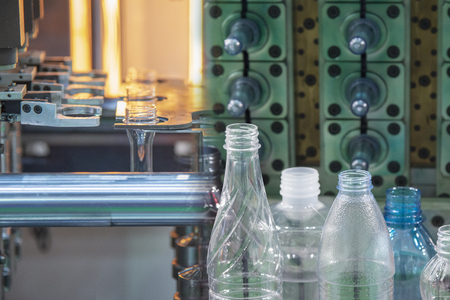 The  abstract scene of preform shape of plastic bottles and plastic bottle products. Drinking water bottle manufacturing process concept.