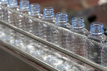 The plastic bottles in the conveyor belt.The drinking water bottles manufacturing process.