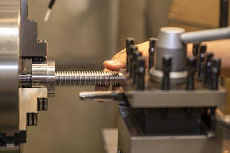 La máquina de torno corta la rosca en el eje de acero. La máquina de torneado hace la rosca en el eje de acero. Foto de archivo