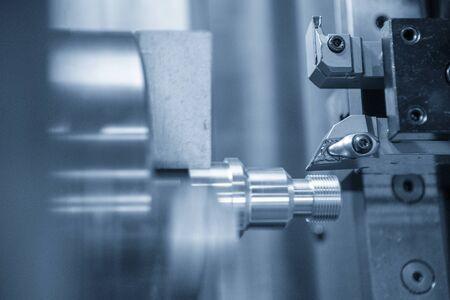 Die CNC-Drehmaschine schneidet das Gewinde am Ende der Metallwelle. Der hochmoderne Herstellungsprozess von Automobilteilen durch Drehmaschine.
