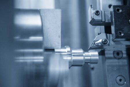La macchina del tornio CNC che taglia il filo all'estremità dell'albero metallico. Il processo di produzione di componenti automobilistici ad alta tecnologia mediante tornio.