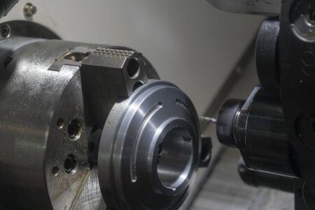 La máquina de torno CNC que fresa la ranura con las piezas del disco de metal. La máquina de torneado y fresado CNC que fabrica las piezas de automóvil con herramientas de fresa plana.