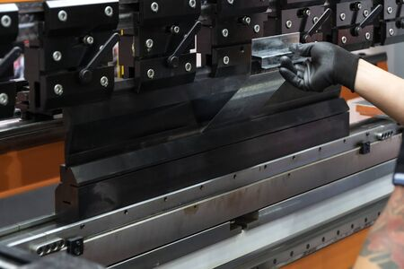 The sheet metal bending machine with hand of operator. The sheet metal forming process with safety concept.