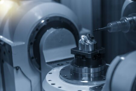 The 5 axis CNC milling machine cutting the turbine blade parts with solid ball end mill tools.The automotive parts manufacturing process by CNC machining center. Stock Photo