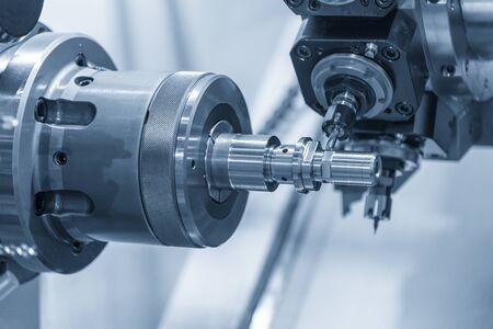 Die Dreh-Fräsmaschine Schneidnut an der Metallwelle. Der High-Tech-Teilefertigungsprozess durch CNC-Drehmaschine.