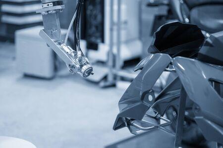 Der Lackierroboter beim Spritzen der Motorradteile. Das automatische System für den Motorradherstellungsprozess durch Roboter.