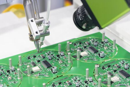 The robotic system for the soldering process with the electronics board. The electronics circuit board manufacturing process by soldering robotic system.