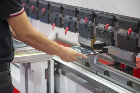 The sheet metal process by bending machine. The skill operator working with the hydraulic bending machine.