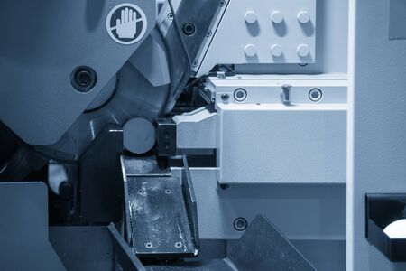 The band saw machine cutting the metal rod. The metal working with the automatic band saw machine. Banco de Imagens