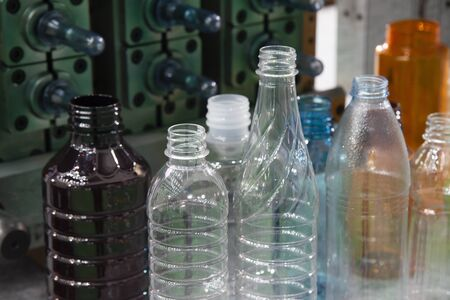 The various type of PET bottle with the injection mould background. The plastic bottle manufacturing process concept. Banco de Imagens