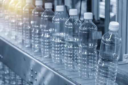The empty plastic bottle in the conveyor belt. The drinking water factory manufacturing process.