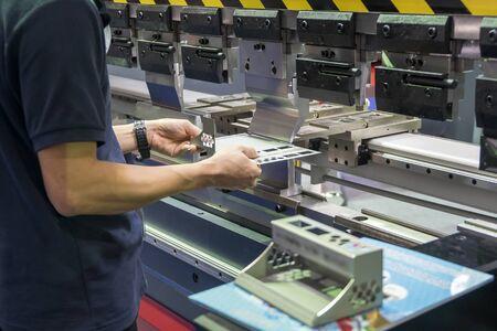 El operador que trabaja con la máquina dobladora hidráulica. El proceso de conformado de chapa mediante máquina dobladora.