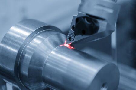 Escena de primer plano de la máquina de torno CNC cortando las piezas del eje de metal. Escena abstracta de la máquina de torneado cortando las piezas del eje.