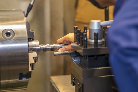 The worker operation with lathe machine. The turning machine cutting the screw shaft parts by skill operator. Stock Photo